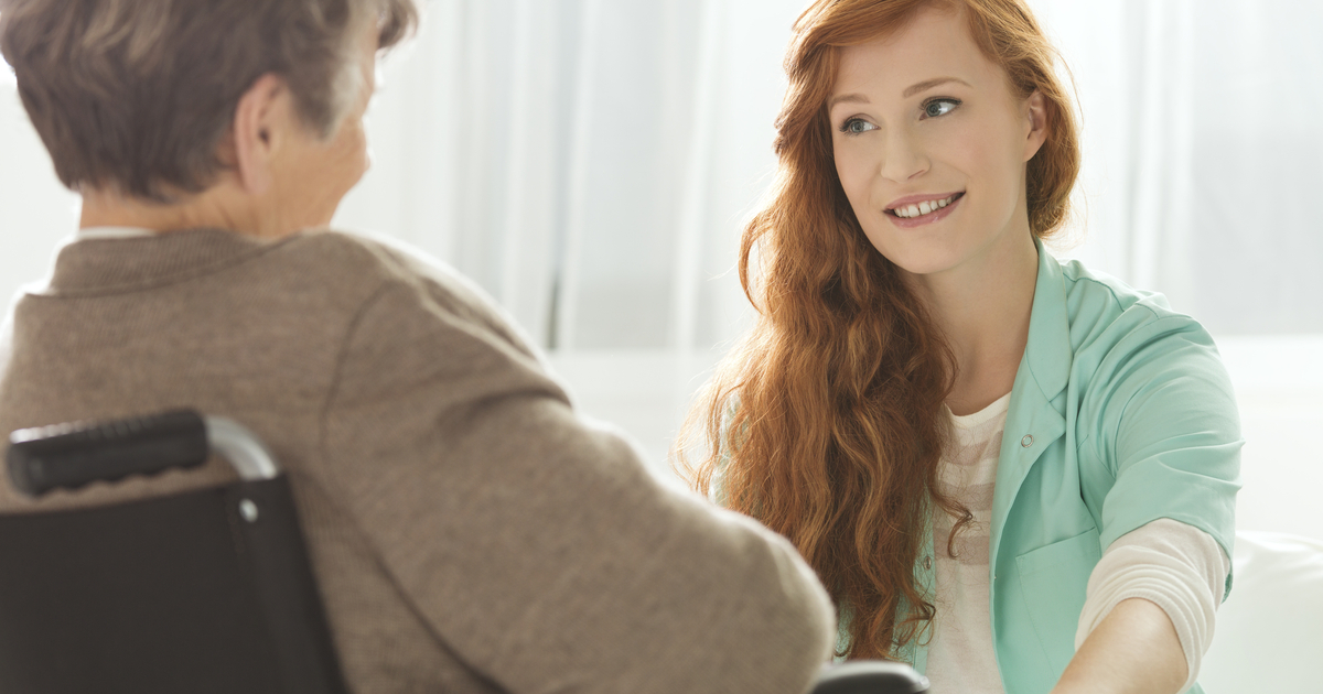 Young woman talking with senior woman in wheelchair